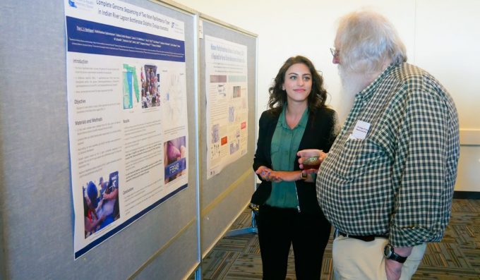 Dr. Thais Rodrigues discusses her research with Dr. Roy Curtiss III at Phi Zeta Day