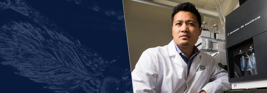 Dr. Dinglasan poses in lab coat